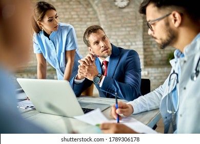 Businessman using laptop while communicating with healthcare workers during the meeting in the office.