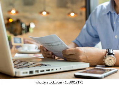 Businessman using laptop while looking at invoice.