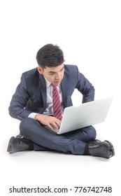 Businessman using laptop while sitting. Isolated on white background.