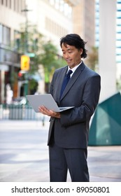 Businessman using laptop while standing on street