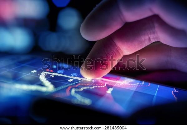 Ein Geschäftsmann, der ein mobiles Gerät verwendet, um Marktdaten zu überprüfen.