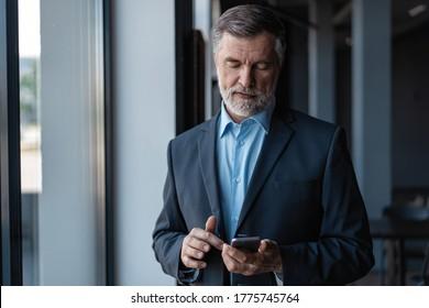 Geschäftsleute, die mobile phone app texting. Reifender Kaukasier, der Smartphone für die Geschäftsarbeit hält