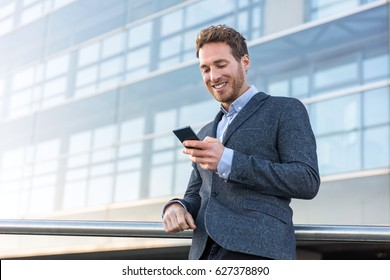 Businessman using mobile phone app texting outside of office in urban city with skyscrapers buildings in the background. Young caucasian man holding smartphone for business work.