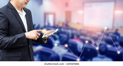 businessman using the mobile phone, blurred of conference hall or seminar room with attendee background. business or education concept.