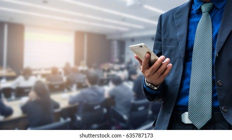 businessman using the mobile phone, blurred of conference hall or seminar room with attendee background. business, people and technology concept.