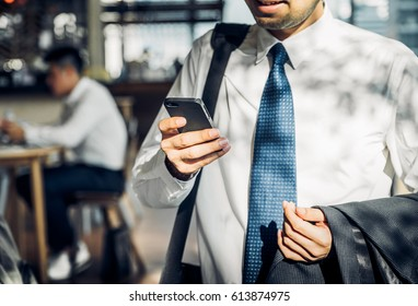 Businessman using mobile phone to chatting with friend after work at corridor office building,selective focus on hand and mobile