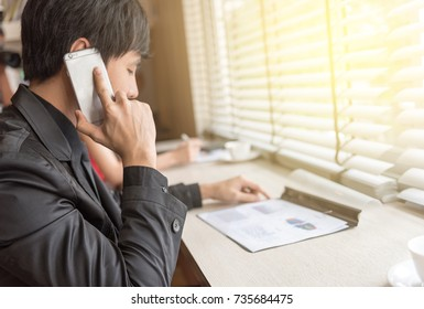 businessman using the mobile phone with graphic document, business people and technology concept.