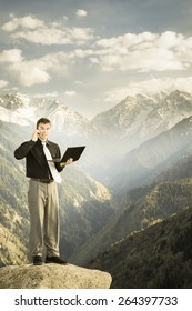 businessman using mobile phone and laptop at the top of mountain