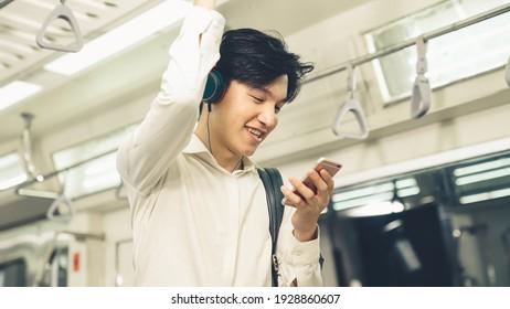 Businessman using mobile phone on public train . Urban city lifestyle commuting concept .
