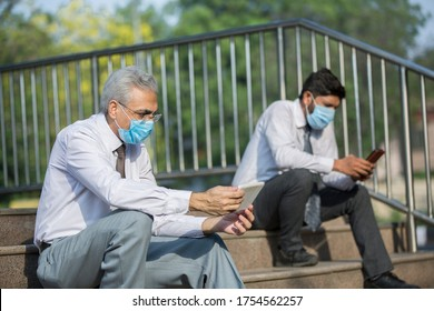 Businessman using mobile phone wearing protective masks and sitting on outside office  while maintaining social distance to protect from COVID-19