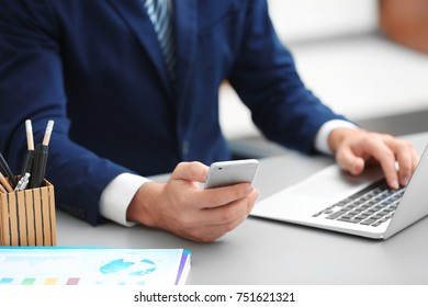 Businessman using mobile phone while working in office