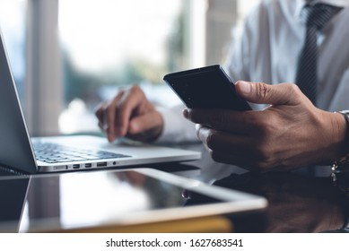 Businessman using mobile smart phone while working on laptop computer with digital tablet on desk. Business man connecting internet, networking in modern office, closeup