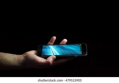 Businessman using modern mobile phone on black background