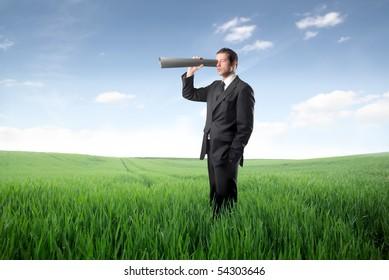 Businessman using a paper tube as binocular