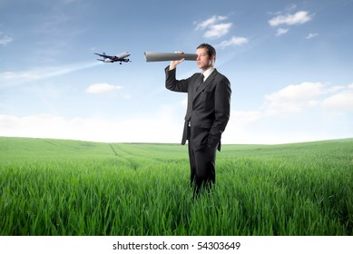 Businessman using a paper tube as binocular and plane on the background