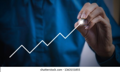 Businessman using pen drawing graphics line growing graph. Describe the organization's management plan or Company and development guidelines. Depicts business growth up continuity plan.