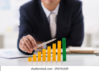 Businessman using pen to indicate ascending bar graph