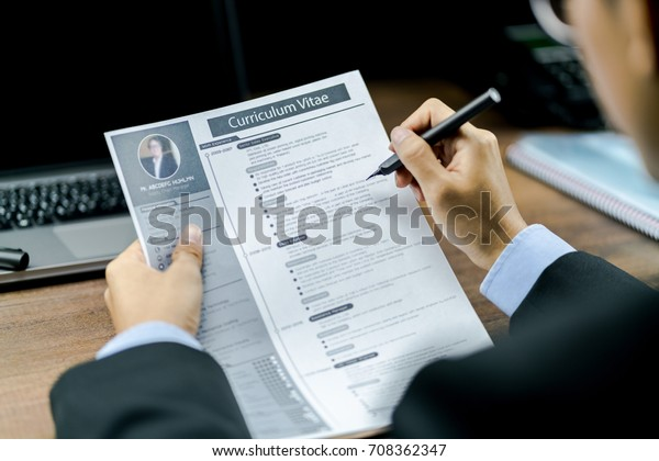 Businessman using the pen to reviewing or checking the Curriculum Vitae or CV of the candidate before interviewing with a laptop and phone on the wood table in background