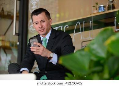Businessman using phone coffee shop