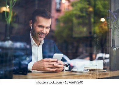Businessman using phone with wireless headphones in cafe