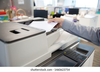 Businessman are using Photocopier and put a paper in a tray of Photocopy machine.