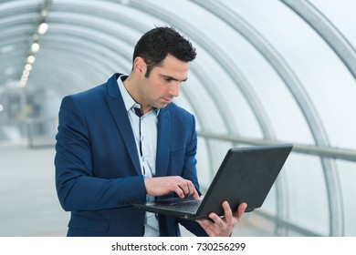 businessman using portable laptop in arched walkway