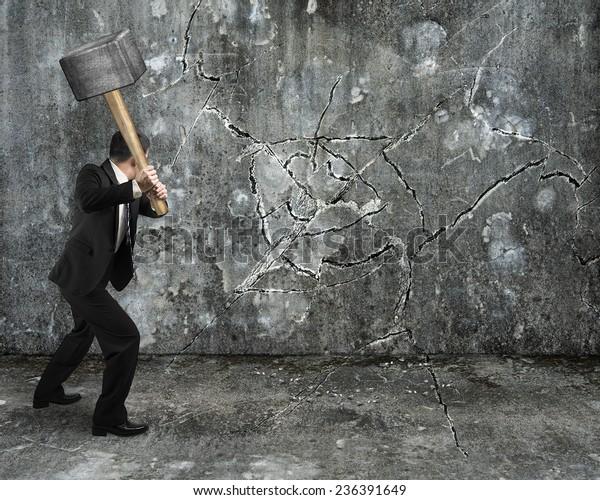 businessman using sledgehammer cracking wall broken on concrete floor background