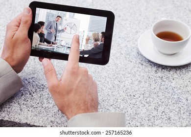 Businessman using small tablet at table against business people in office at presentation