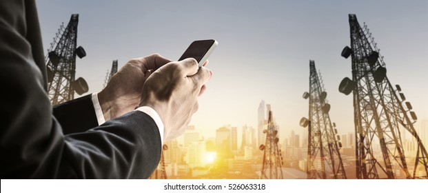 Businessman using smart phone with blurred defocus double exposure panoramic cityscape and telecommunication towers in sunrise