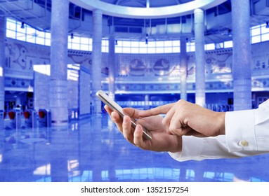 Businessman using smart phone in front of the subway station background