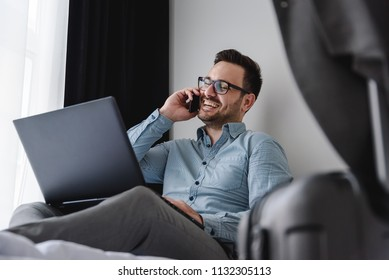 Businessman using smart phone and laptop computer at hotel room. Traveling for work.