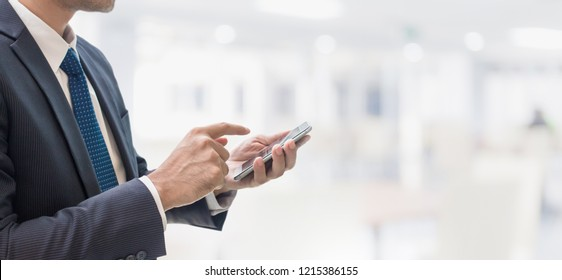 Businessman using smart phone in office space interior background and copy space.Concept of people using mobile online technology.