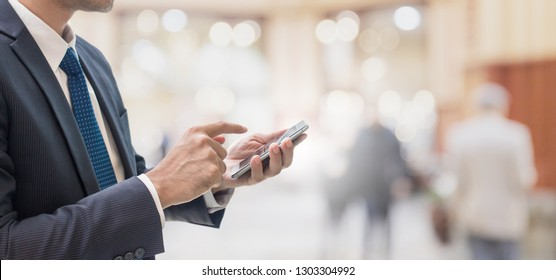 Businessman using smart phone in shopping mall space background and copy space.Concept of people shopping online technology.