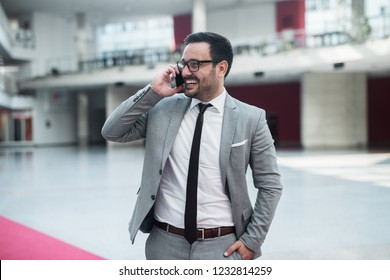 Businessman using smart phone and standing in the hall with hand in the pocket.