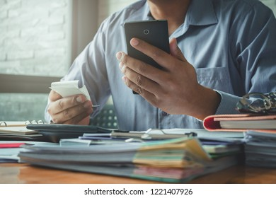 Businessman using smartphone and calculate bills in office.
