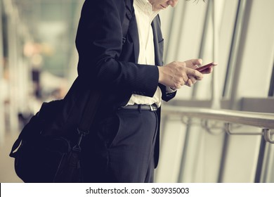 Businessman using smartphone in Changi airport.