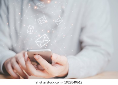 Businessman using smartphone with e-mail icon , technology concept.