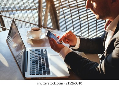 businessman using smartphone and laptop