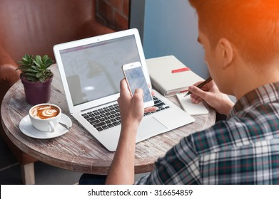 Businessman using smartphone and laptop writing on tablet on wooden table in coffee shop with a cup of coffee
