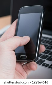 Businessman using smartphone on laptop's background, hand closeup