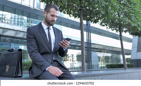 Businessman Using Smartphone for Reading Email