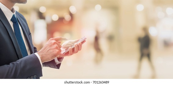 Businessman using smartphone in shopping mall space background and copy space.