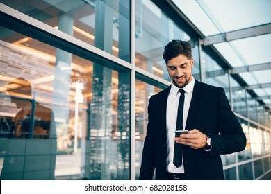 Businessman using smartphone and smiling at airport. Young business executive with mobile phone at airport.