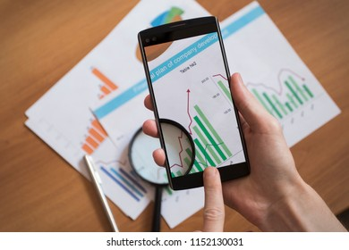 Businessman using smartphones to take photos of document and diagram, business chart.