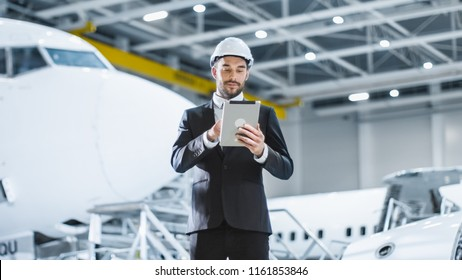 Businessman using Tablet in Aircraft Maintenance Terminal