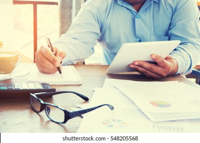 Businessman using a tablet to analysis marketing.