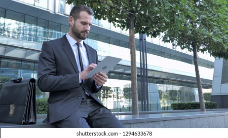 Businessman Using Tablet Computer while Sitting Outside Office