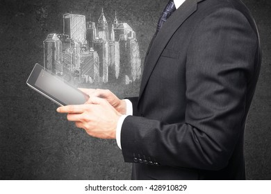 businessman using tablet and drawing highrise on wall