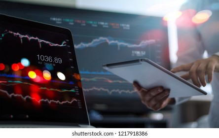 Businessman using tablet and laptop for analyzing data stock market in monitoring room background, forex trading graph, stock exchange trading online, financial investment concept.