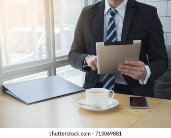 Businessman using tablet and latte coffee white cup on wooden table in cafe